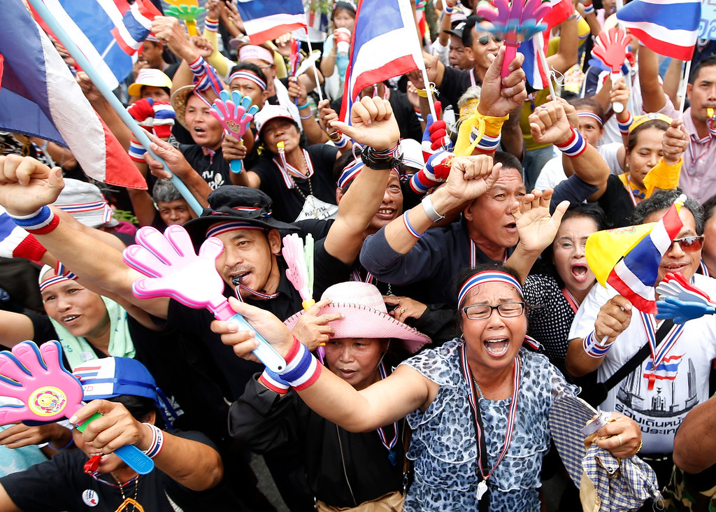 . Thai anti-government protesters shout slogans during a rally occupying the Finance Ministry in Bangkok, Thailand, 26 November 2013. Tens thousands of anti-government protesters on 26 November 2013 took over four more ministries, the Agriculture and Cooperatives Ministry, the Tourism and Sports Ministry, the Transport Ministry and the Interior Ministry after occupied parts of the Finance Ministry and Foreign Ministry aimed to paralyze the government of Prime Minister Yingluck Shinawatra.  EPA/RUNGROJ YONGRIT