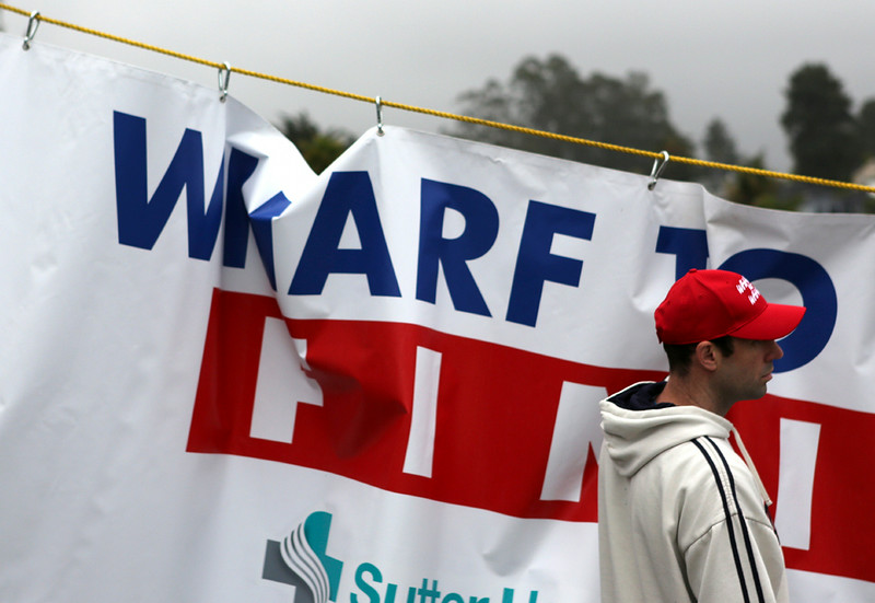 . Wharf to Wharf officials raise the finish line banner in Capitola on Sunday. (Kevin Johnson -- Santa Cruz Sentinel)