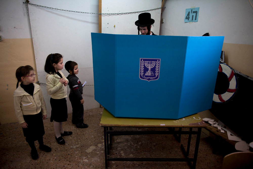 Description of . An Ultra-orthodox Jewish man votes as his children stand near him, in Bnei Brak, Israel, during legislative elections Tuesday, Jan. 22, 2013.  Israelis began trickling into polling stations Tuesday morning to cast their votes in a parliamentary election expected to return Prime Minister Benjamin Netanyahu to office despite years of stalled peacemaking with the Palestinians and mounting economic troubles. Polls indicate about a dozen of 32 parties competing in Tuesday's election have a chance of winning seats in the 120-member parliament. Most parties fall either into the right-wing-religious or center-left camp, and surveys indicate hard-line and ultra-Orthodox Jewish parties will command a majority. (AP Photo/Oded Balilty)