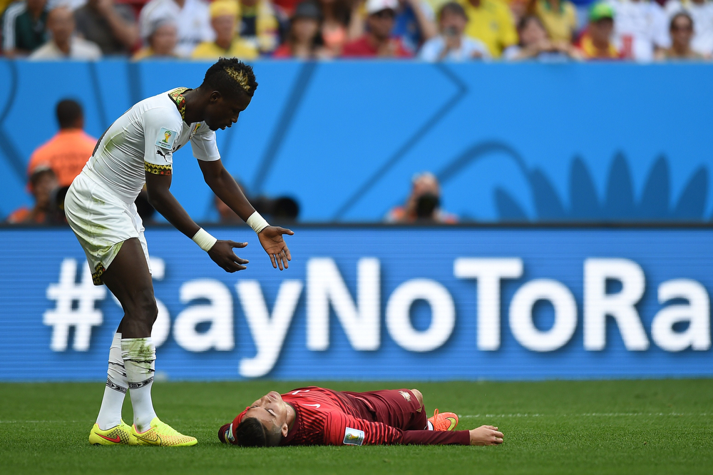 . Ghana\'s defender John Boye (L) reacts as Portugal\'s forward and captain Cristiano Ronaldo lies on the ground during to the Group G football match between Portugal and Ghana at the Mane Garrincha National Stadium in Brasilia during the 2014 FIFA World Cup on June 26, 2014. (CARL DE SOUZA/AFP/Getty Images)