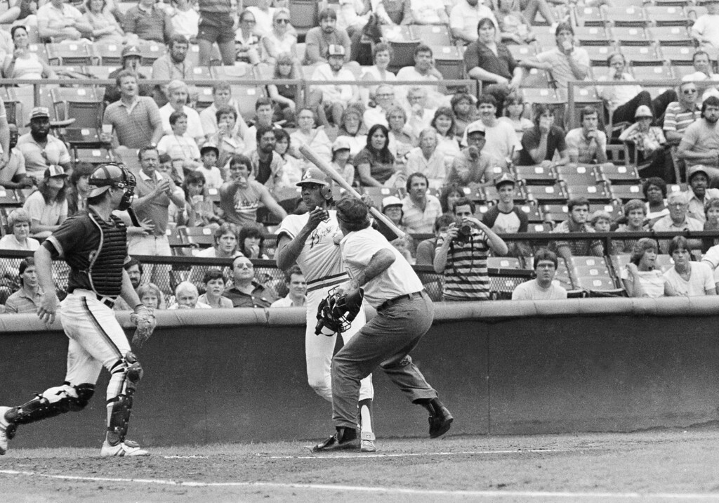 . Homeplate umpire Steve Rippley clutches the jersey of Atlanta Braves batter Pascual Perez as he brandished his bat after a brushback pitch by Ed Whitson of the Sand Diego Padres, Aug. 13, 1984 at Atlanta Fulton County Stadium. Perez opened the game hitting Alan Wiggins with his first pitch. Brawls erupted after Perez was hit by Padres relief pitcher Craig Lefferts. The Braves won the game, 5-3. (AP Photo/Charles Kelly)