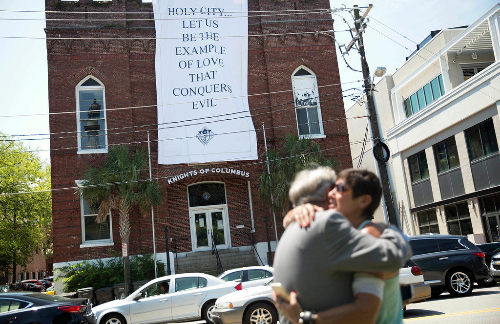 . A banner hangs from a local business as residents Mari Fisher, right, and John Tecklenburg embrace upon meeting on the street near the Emanuel AME Church, Saturday, June 20, 2015, in Charleston, S.C. (AP Photo/David Goldman)