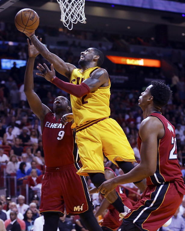 . Cleveland Cavaliers guard Kyrie Irving (2) shoots over Miami Heat forward Luol Deng (9) and Hassan Whiteside (21) during the first half of an NBA basketball game, Saturday, March 19, 2016, in Miami. (AP Photo/Lynne Sladky)