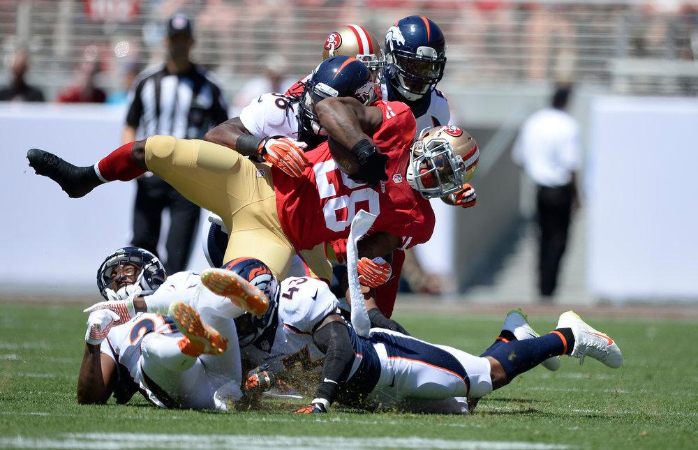 . San Francisco 49ers running back Carlos Hyde (28) gets upended by Denver Broncos cornerback Aqib Talib (21) Denver Broncos strong safety T.J. Ward (43) and Denver Broncos outside linebacker Nate Irving (56) during the first quarter August 17, 2014 at Levi\'s Stadium. (Photo by John Leyba/The Denver Post)