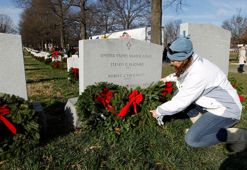 . Volunteer Carol Ann Cerkan laysholiday wreaths over the graves of fallen soldiers during Wreaths Across America Day at Arlington Cemetery on Saturday Dec. 10, 2011.(AP Photo/Jose Luis Magana)
