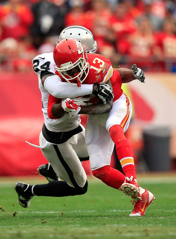 . KANSAS CITY, MO - DECEMBER 14:   De\'Anthony Thomas #13 of the Kansas City Chiefs runs the ball against  Charles Woodson #24 of the Oakland Raiders during the first quarter at Arrowhead Stadium on December 14, 2014 in Kansas City, Missouri.  (Photo by Jamie Squire/Getty Images)
