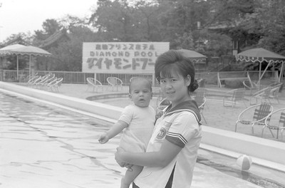 One of the hotel's workers holding David.  This is the pool at one of the Tokyo hotels where I would put up Fairchild visitors/engineers when they came to Tokyo.  The hotel staff got to recognize us and allowed Martha to bring the kids during the hot and humid summer days in Tokyo.  1965