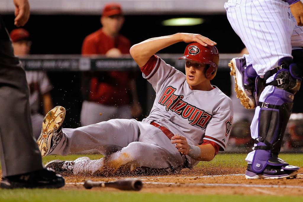 . DENVER, CO - SEPTEMBER 18:  Nick Ahmed #13 of the Arizona Diamondbacks slides home to score on a two RBI single by Ender Inciarte #5 of the Arizona Diamondbacks off of starting pitcher Yohan Flande #58 of the Colorado Rockies to give the Diamondbacks a 2-1 lead in the third inning at Coors Field on September 18, 2014 in Denver, Colorado.  (Photo by Doug Pensinger/Getty Images)