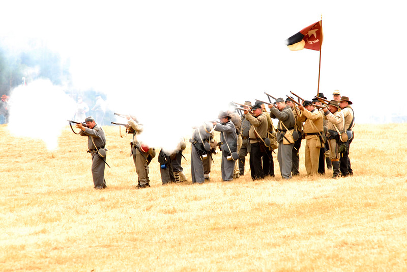 Confederate infantry reenactors return fire on a field obscured by smoke from artillery fire. The Skirmish at Gamble's Hotel happened on March 5, 1885 when 500 federal soldiers, under the command of Reuben Williams of the 12th Indiana Infantry, marched into Florence to destroy the railroad depot but were met by Confederate soldiers backed up with 400 militia. The reenactment, held by the 23rd South Carolina Infantry, was held at the Rankin Plantation in Florence, South Carolina on Saturday, March 5, 2011. Photo Copyright 2011 Jason Barnette