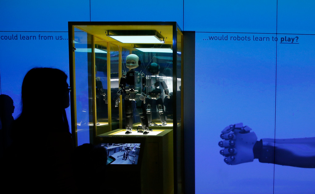 . A member of the media watches a digital display that asks \'Would robots learn to play?\', during a press preview for the Robots exhibition held at the Science Museum in London, Tuesday, Feb. 7, 2017. The exhibition which shows 500 years of mechanical and robotic advances is open to the public form Feb. 8 through to Sept. 3. (AP Photo/Alastair Grant)