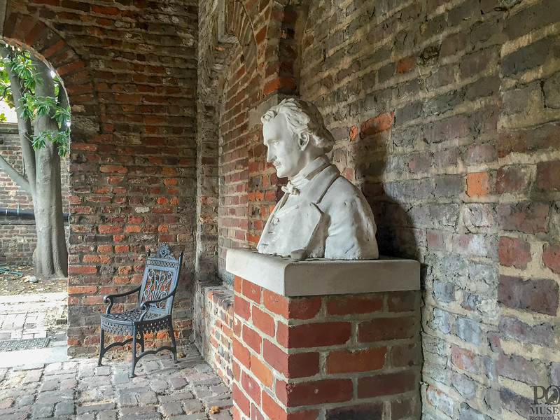Edgar Allen Poe bust stands against a brick wall in the Edgar Allan Poe Museum.