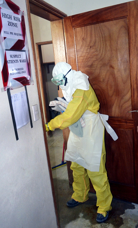 . A picture taken on July 24, 2014 shows a staff member of the Christian charity Samaritan\'s Purse wearing protective whilst entering a room where patients are kept in the ELWA hospital in the Liberian capital Monrovia. An American doctor battling West Africa\'s Ebola epidemic has himself fallen sick with the disease in Liberia, Samaritan\'s Purse said on July 27. AFP PHOTO / ZOOM DOSSO