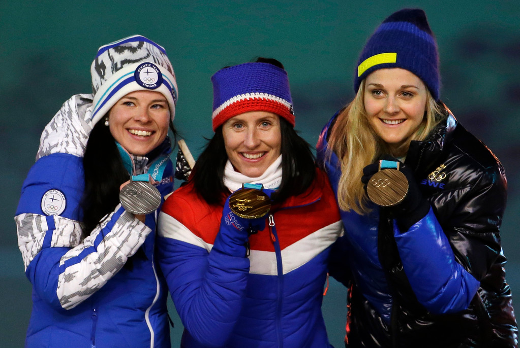 . From left, Finland\'s Krista Parmakoski, silver, Norway\'s Marit Bjoergen, gold, and Sweden\'s Stina Nilsson, bronze, pose for photos during the medals ceremony for the women\'s 30k cross-country skiing at the closing ceremony of the 2018 Winter Olympics in Pyeongchang, South Korea, Sunday, Feb. 25, 2018. (AP Photo/Natacha Pisarenko)