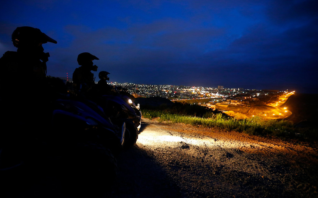 . U.S. Customs and Border Patrol agents sit on their ATVs atop a hill overlooking Tijuana, Mexico during a night patrol along the international border between Mexico and the United States, March 26, 2013. Picture taken March 26, 2013. REUTERS/Mike Blake