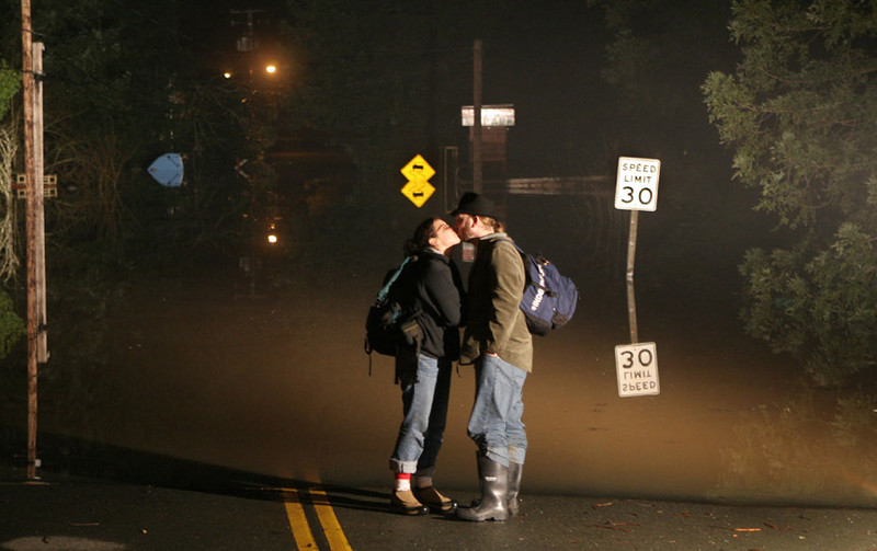 Jacqueline Iraola shares a kiss with her boyfriend Dustin Gooler while waiting for a rowboat ride across a flooded street next to the Russian River in Guerneville, Calif, late Saturday Dec. 31, 2005.   The river was cresting at the beginning of the New Year.  (AP Photo/Dino Vournas)