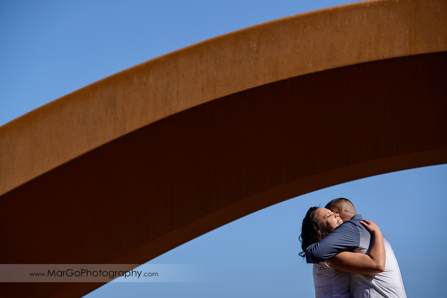 engagement session at Rincon Park in San Francisco - couple hugging under the Bow and Arrow