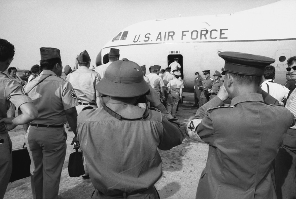 . Viet Cong and North Vietnamese members of the joint military commission (foreground) snap pictures of U.S. troops as they board an Air Force plane for the flight home from Saigon\'s Tan Son Nhut Air Base, March 27, 1973. Withdrawal of these and other U.S. military personnel resumed after it was delayed to insure release of American POWs captured in Laos. (AP Photo/Neal Ulevich)