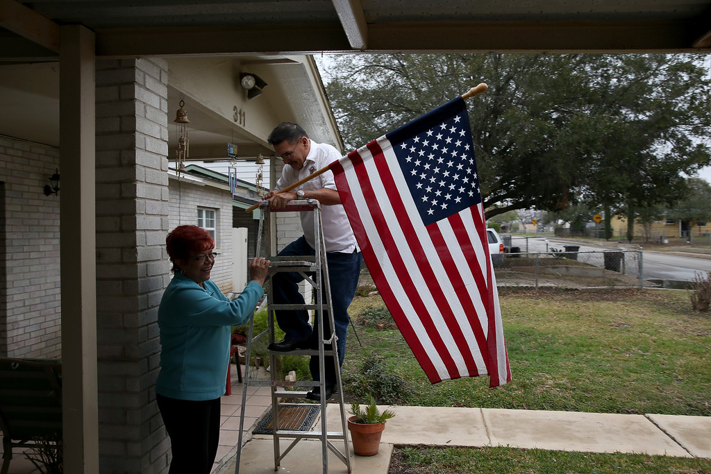 . U.S. Army Specialist Four Santiago J. Erevia with the help of his wife, Leticia Erevia, hangs his American flag from its place on his house as he waits to receive the Medal of Honor at the White House on March 18th for his actions while serving in the Vietnam war on March 11, 2014 in San Antonio, Texas.  (Photo by Joe Raedle/Getty Images)