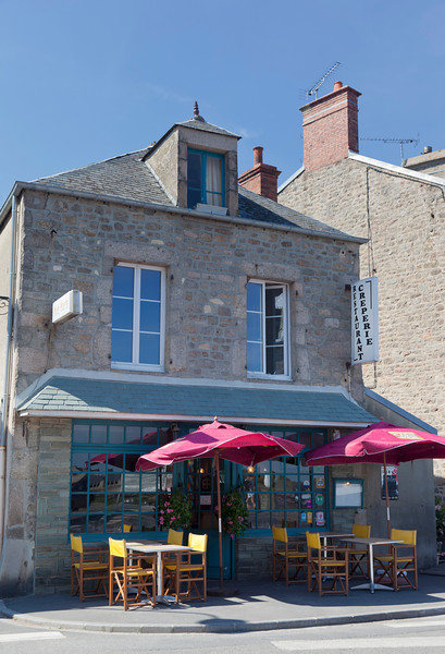 """Barfleur, France - July 3, 2011: Restaurant and Creperie """"Chez Buck"""" in traditional granite house in Barfleur, France. Barfleur is a picturesque fishing village on the peninsula Cotentin in Basse Normandy. In the middle ages Barfleur was one of the chief ports for embarkation for England."""