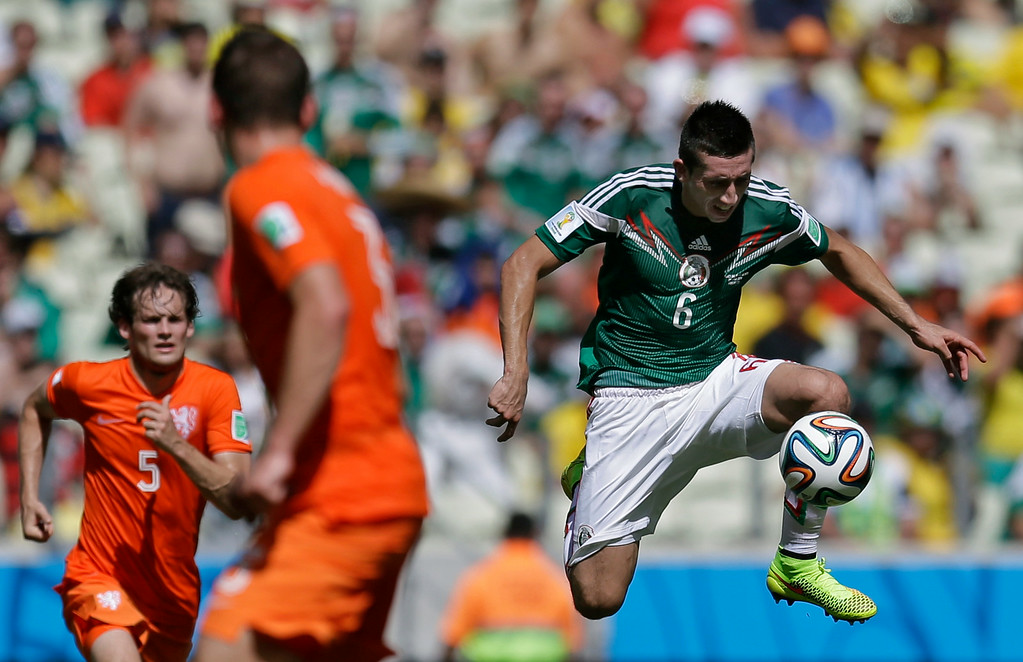 . Mexico\'s Hector Herrera, right, controls the ball during the World Cup round of 16 soccer match between the Netherlands and Mexico at the Arena Castelao in Fortaleza, Brazil, Sunday, June 29, 2014. (AP Photo/Natacha Pisarenko)