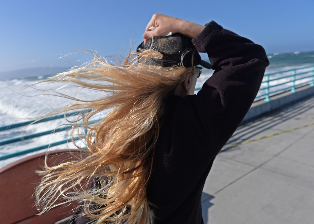 . It was a bad hair day along the coast Monday with high winds and flowing locks. Karen Payne holds onto her hat as her long blonde locks fly in the wind on the Manhattan Beach Pier. Photo by Brad Graverson 4-8-13