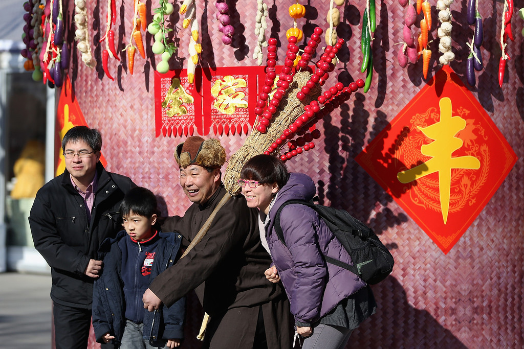 . A Chinese family pose for photos with a folk artist at the Spring Festival Temple Fair for celebrating Chinese Lunar New Year of Horse at the Temple of Earth park on January 30, 2014 in Beijing, China.   (Photo by Feng Li/Getty Images)