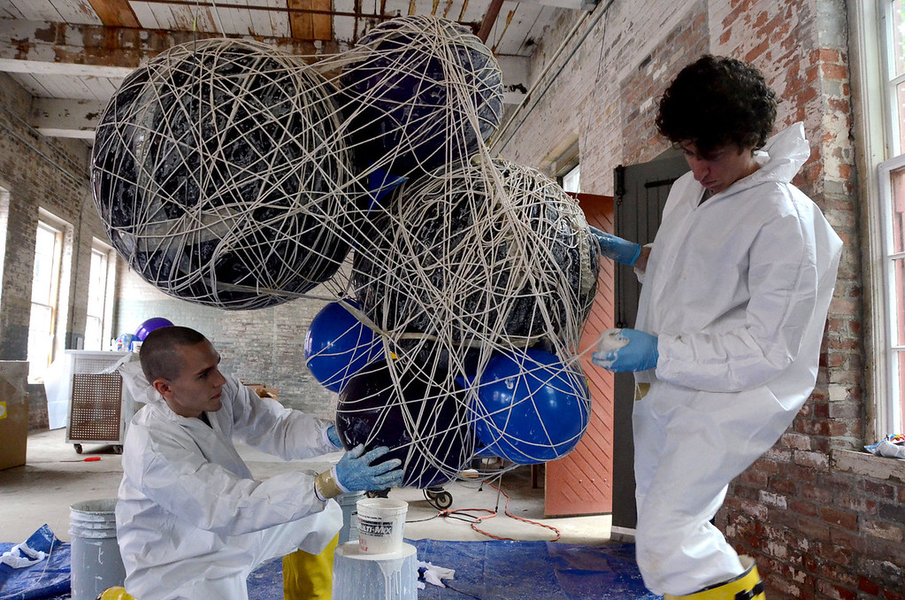 . Gillian Jones/North Adams Transcript Jackson Kleiser, left, assists Jeremy Roth, who does lighting visual production and design, with making string lamps or \'clouds\' that will hang over the stage during the Solid Sound weekend at Mass MoCA starting on Friday.