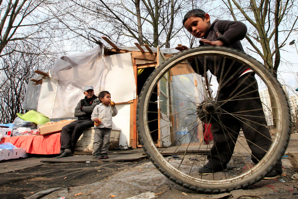 . A Roma boy plays with a bicycle wheel during International Roma Day in an illegal camp in Lille, northern France on April 8, 2013.   REUTERS/Pascal Rossignol