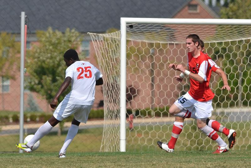 Denzel Clarke (25) kicks the ball hard for a goal.