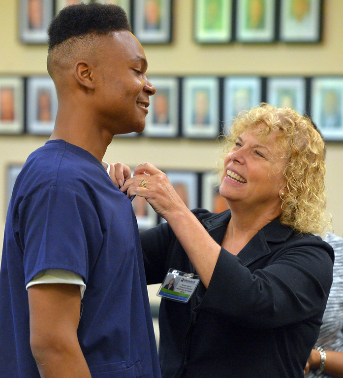 . R.N. Susan Gavel pins Daniel Scott as he and nine other recent high school graduates received their Certified Nursing Assistant certificates at the Goodwill in Long Beach, CA on Friday, August 22, 2014. The students; Gabriela Avila, Averianna Burnett, Alesia Clay, Ariana Mays, Kendra Montano, Silvia Monzon, Genesis Perez, Cindia Sanchez, Daniel Scott and Dahlia You completed the year-long course in a partnership between the LBUSD and Goodwill. This is the first year that the state Certified Nurse Assistant Training Academy program has been free for the students. It was announced to the families and friends gathered that all 10 of the graduates have health care job interviews next week. (Photo by Scott Varley, Daily Breeze)