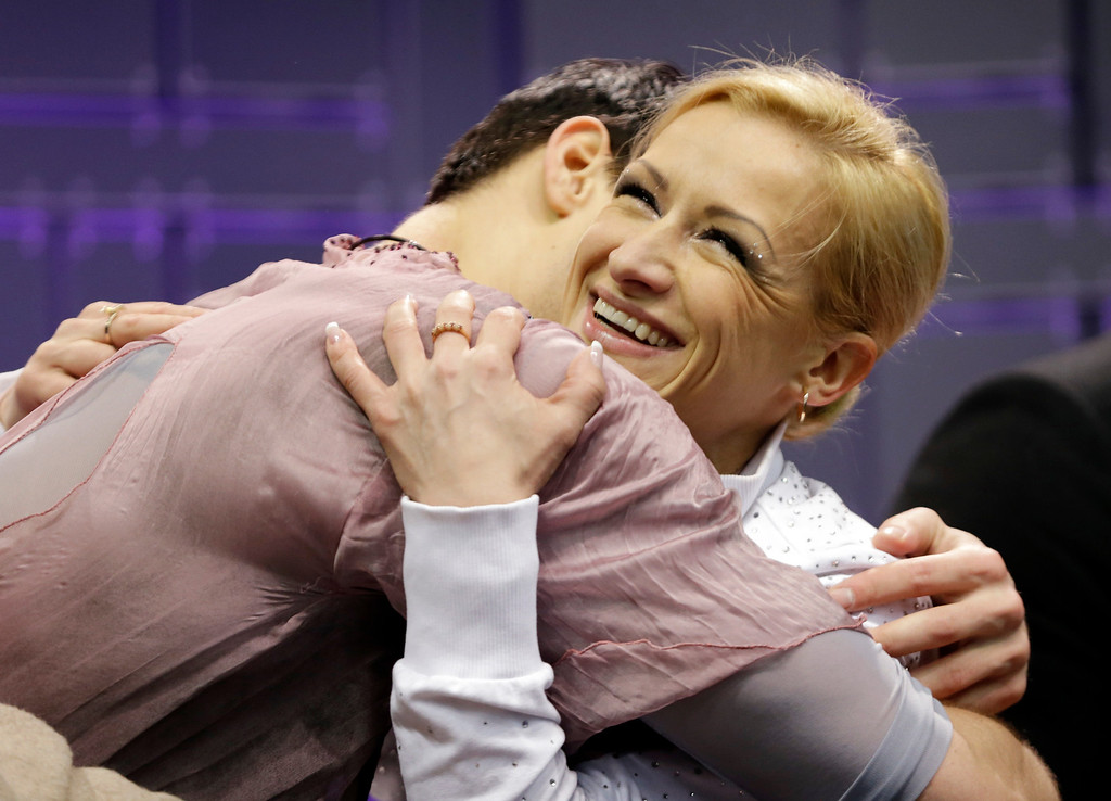 . Tatiana Volosozhar and Maxim Trankov, of Russia, react as they watch their scores during the pairs free skate program at the World Figure Skating Championships Friday, March 15, 2013, in London, Ontario. (AP Photo/Darron Cummings)