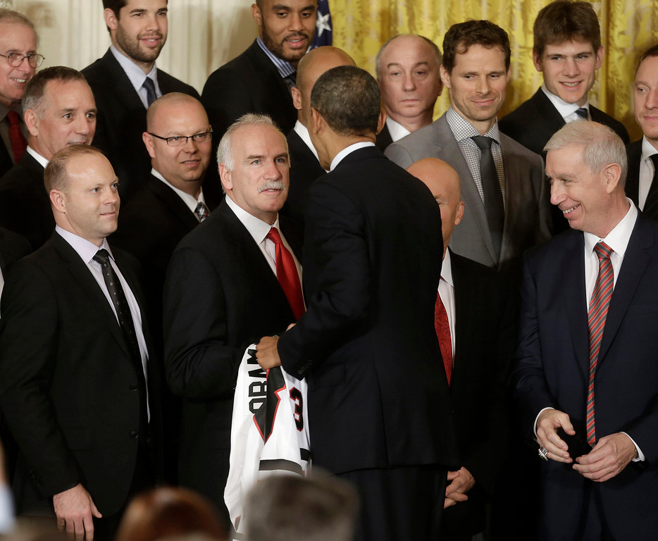 . President Barack Obama shakes hands with Chicago Blackhawks head coach Joel Quenneville on stage during a ceremony where he honored the NHL 2013 Stanley Cup champion Chicago Blackhawks hockey team, Monday, Nov. 4, 2013, in the East Room of the White House in Washington.  Obama welcome the five-time Stanley Cup Champion to honor the team and their 2013 Stanley Cup victory over the Boston Bruins. From left are, Vice President-General Manager Stan Bowman, Quenneville, the president and President and CEO John McDonough. (AP Photo/Pablo Martinez Monsivais)