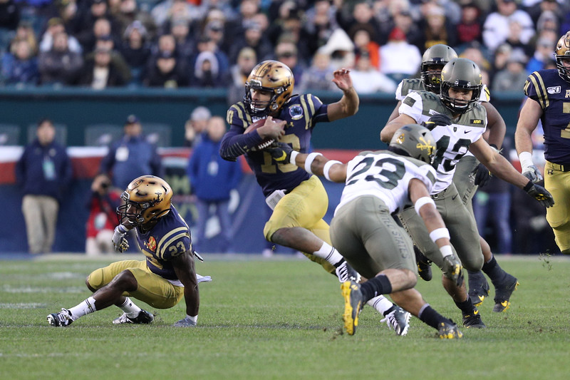 Navy quarterback #10 Malcolm Perry slips past an arm tackle by Army #23 Elijah Riley.