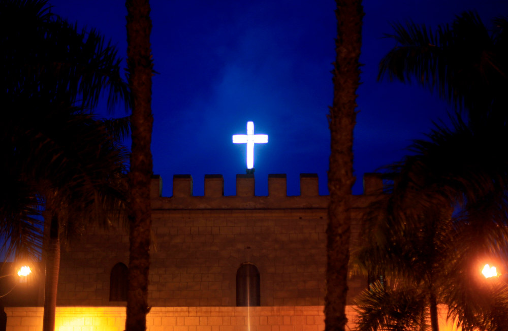 Description of . A cross stands over the gate of the historic al-Muharraq Monastery, a centuries-old site some 180 miles (300 kilometers) south of Cairo in the province of Assiut, Egypt, Tuesday, Feb. 5, 2013. Egypt\'s Coptic Christian pope sharply criticized the country\'s Islamist leadership in an interview with The Associated Press on Tuesday, saying the new constitution is discriminatory and Christians should not be treated as a minority. (AP Photo/Khalil Hamra)