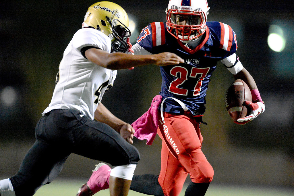. La Salle\'s running back Milan Acquaah (27) gains yards as they play Bishop Montgomery during the first quarter in Friday night\'s football game at La Salle High School in Pasadena, October 25, 2013.  (Photo by Sarah Reingewirtz/Pasadena Star-News)