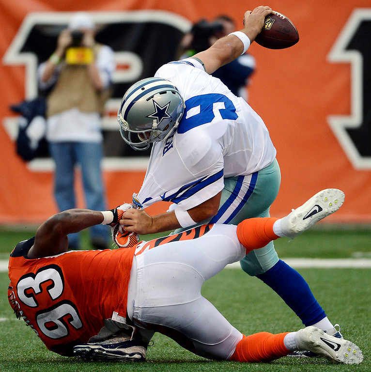 . Dallas Cowboys quarterback Tony Romo (9) is sacked by Cincinnati Bengals defensive end Michael Johnson (93) in the first half of an NFL football game, Sunday, Dec. 9, 2012, in Cincinnati. (AP Photo/Michael Keating)