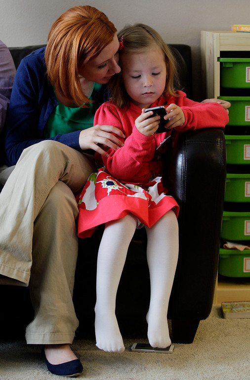 . Coy Mathis plays with a smart phone as her mother, Kathryn, watches, at their home in Fountain, Colo., Monday Feb. 25, 2013.  (AP Photo/Brennan Linsley)