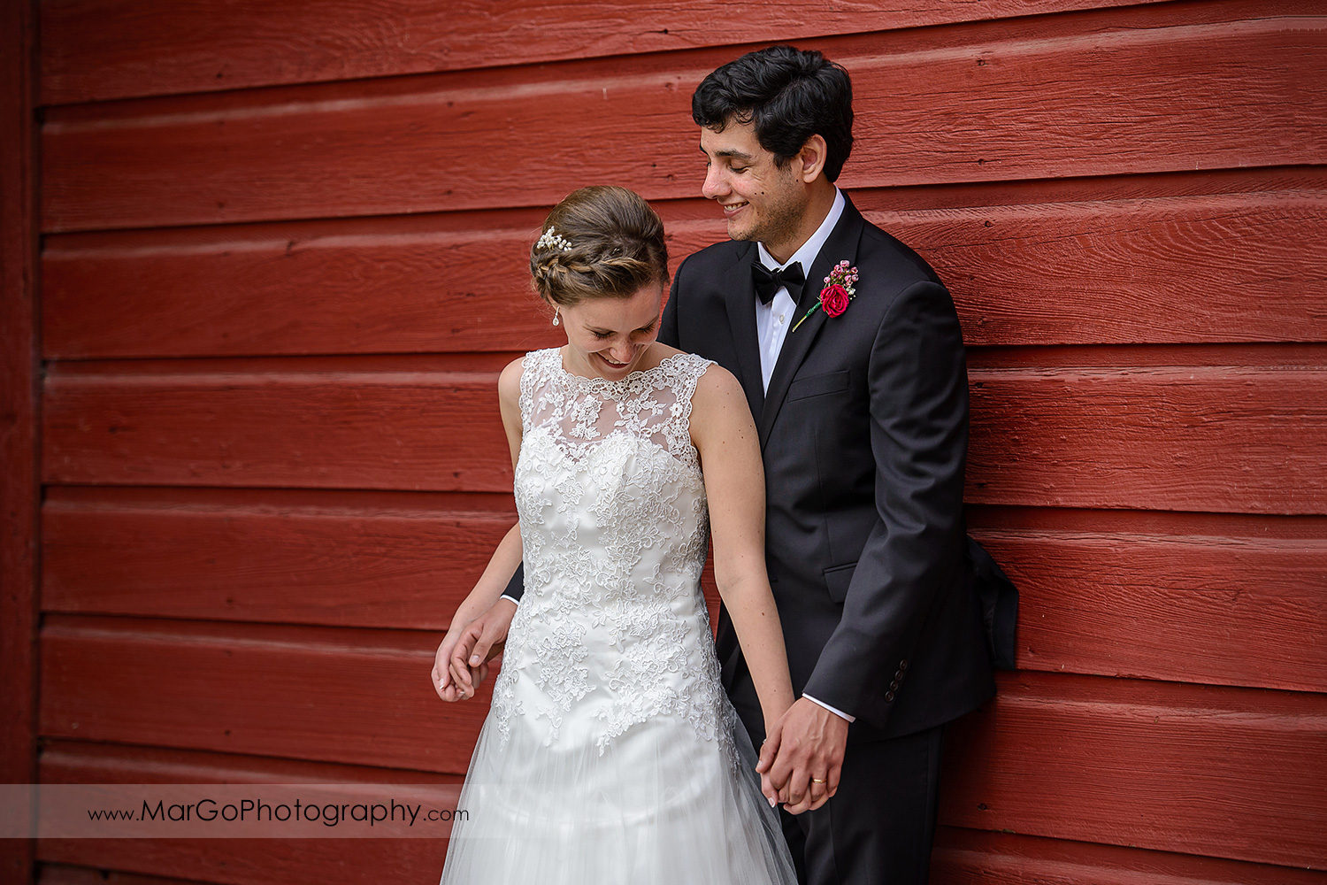 bride and groom laughing at red barn wall during bridal session at Shinn Historical Park and Arboretum in Fremont