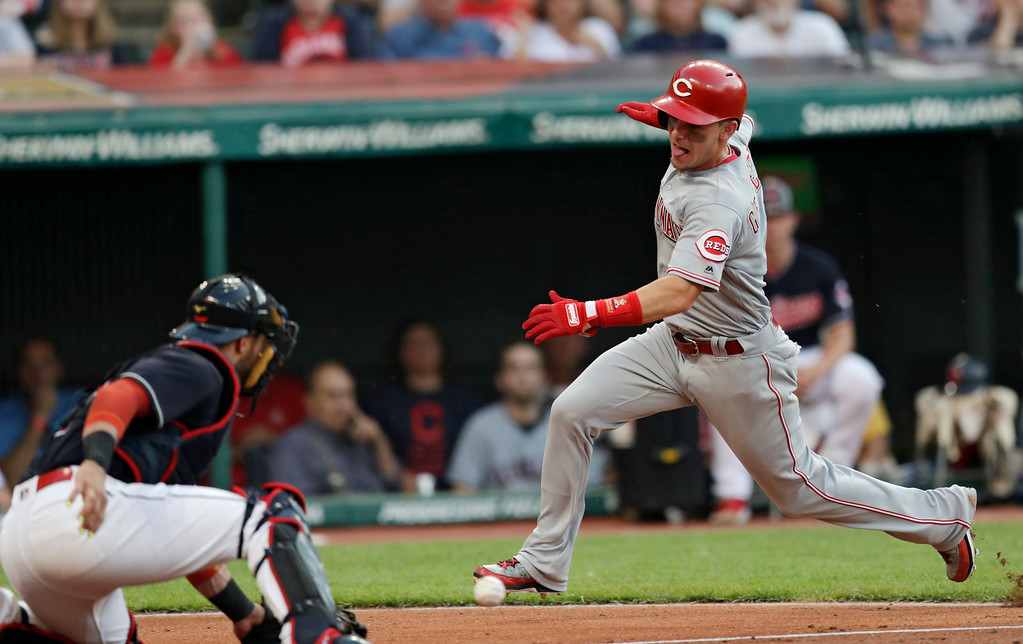 . Cincinnati Reds\' Scooter Gennett, right, slides into home plate to score as Cleveland Indians\' Yan Gomes can\'t hold onto the ball in the fourth inning of a baseball game, Monday, July 9, 2018, in Cleveland. (AP Photo/Tony Dejak)