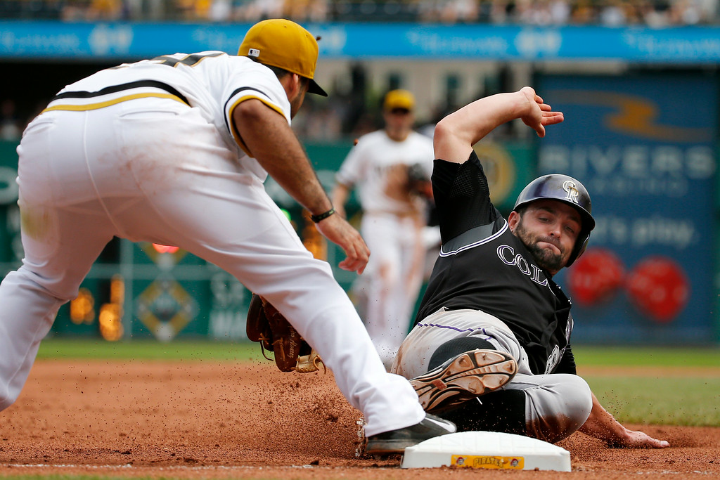 . Colorado Rockies\' Michael McKenry, right, is forced out at third base by Pittsburgh Pirates third baseman Pedro Alvarez on a fielder\'s choice by Rockies\' Brandon Barnes during the seventh inning of a baseball game in Pittsburgh on Sunday, July 20, 2014. The Pirates won 5-3. (AP Photo/Gene J. Puskar)