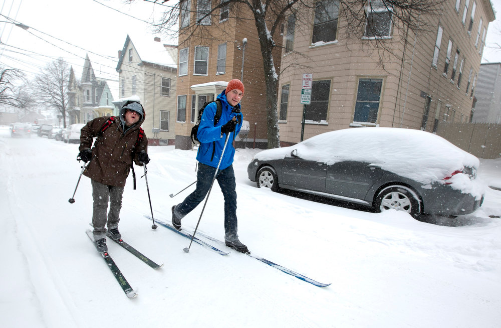 . Andre Tranchemantague, left, and Will Guerette, ski on a snow-covered road as they make there way to a bar during the early stages of a snow storm, Friday, Feb. 8, 2013, in Portland, Maine.  A snowstorm sweeping into Maine already has dumped half-a-foot of snow around Portland and contributed to a 19-car pileup. And it\'s just getting started. Chris Legrow from the National Weather Service says a blizzard warning is issued Friday evening for the southern coast, when the main storm arrives. The forecast calls for up to 2 feet of snow and winds gusting to 50 mph. (AP Photo/Robert F. Bukaty)