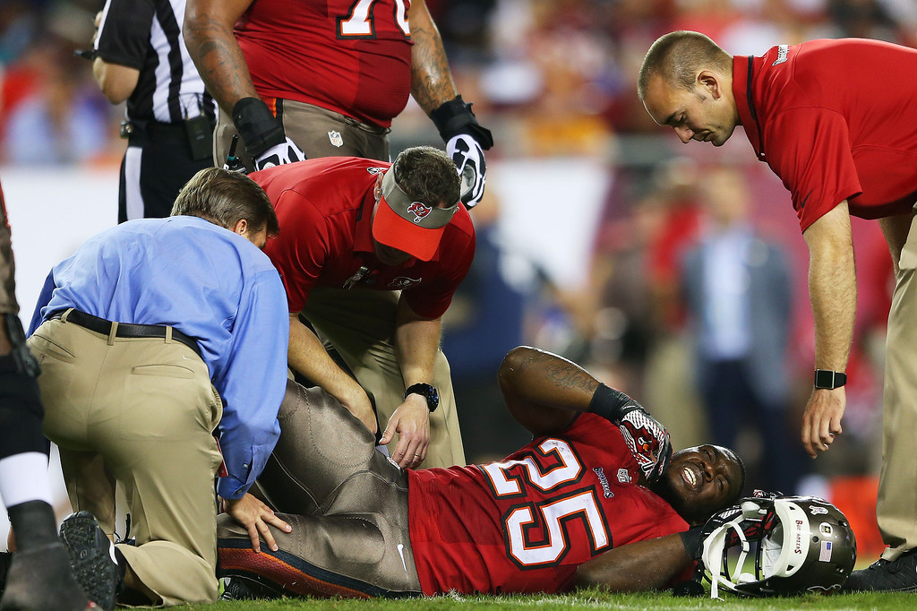 . Mike James #25 of the Tampa Bay Buccaneers receives medical attention after being injured in the first quarter against the Miami Dolphins at Raymond James Stadium on November 11, 2013 in Tampa, Florida.  (Photo by Mike Ehrmann/Getty Images)