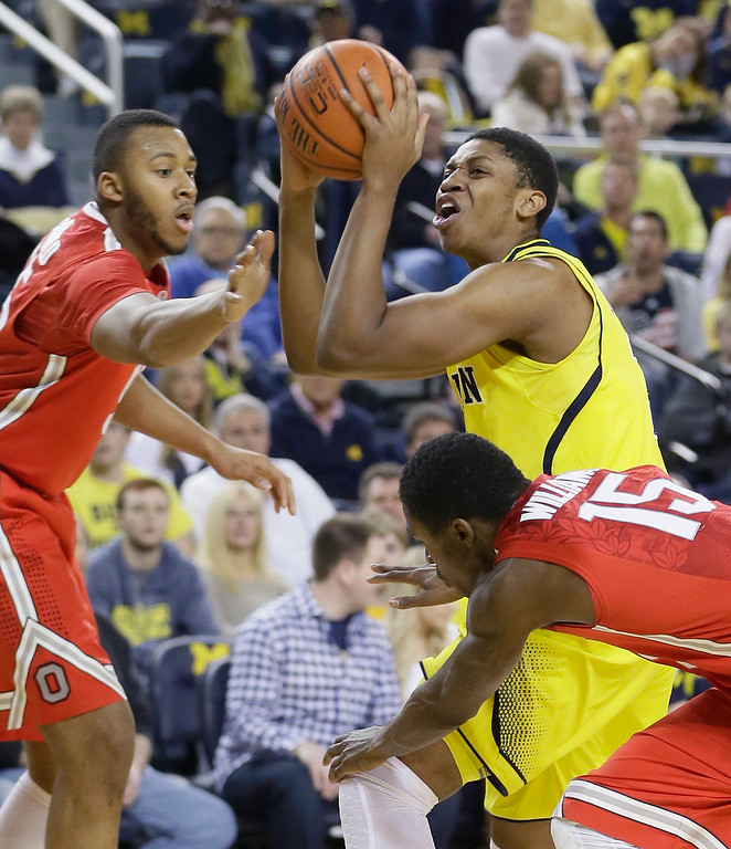 . Michigan guard Kameron Chatman, right, shoots between the defense of Ohio State center Trey McDonald, left, and guard Kam Williams during the first half of an NCAA college basketball game, Sunday, Feb. 22, 2015 in Ann Arbor, Mich. (AP Photo/Carlos Osorio)