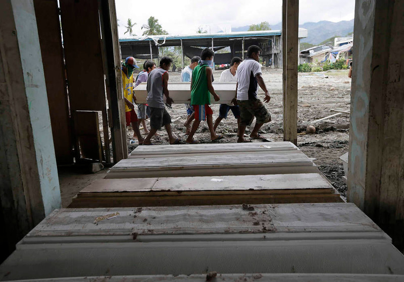 . Relatives carry for burial their next of kin, one of the victims of typhoon Bopha, at New Bataan township, Compostela Valley in southern Philippines Saturday Dec. 8, 2012. Search and rescue operations following a typhoon that killed nearly 600 people in the southern Philippines have been hampered in part because many residents of this ravaged farming community are too stunned to assist recovery efforts, an official said Saturday. (AP Photo/Bullit Marquez)