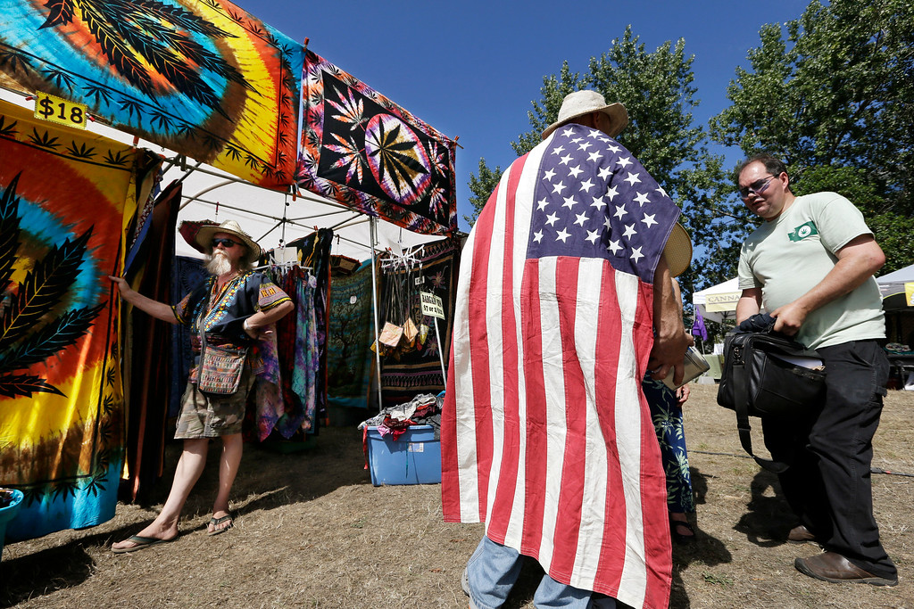 . A man wears an American flag as he walks past a vendor selling tie-dyed products at the first day of Hempfest, Friday, Aug. 16, 2013, in Seattle. Thousands packed the Seattle waterfront park for the opening of a three-day marijuana festival ó an event that is part party, part protest and part victory celebration after the legalization of pot in Washington and Colorado last fall. Hempfest was expected to draw as many as 85,000 people per day. (AP Photo/Elaine Thompson)