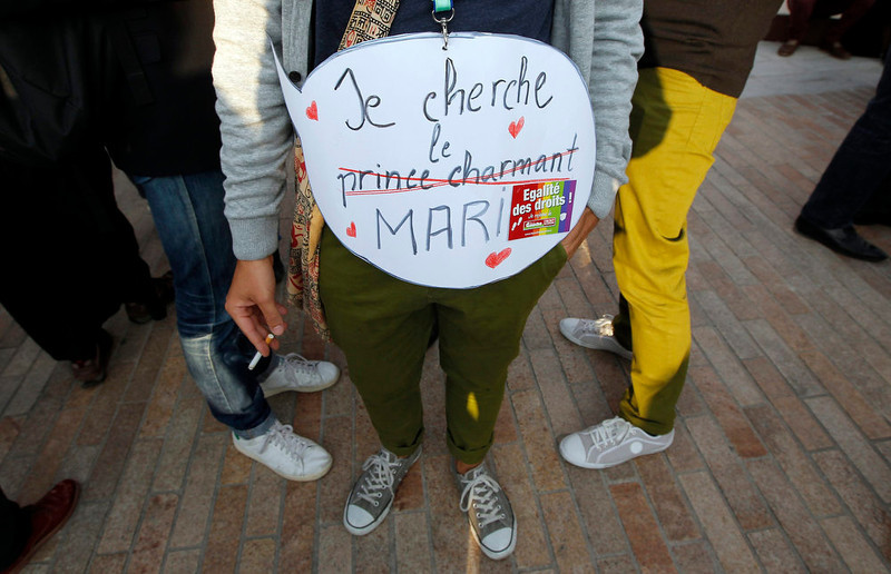 """. People gather outside Marseille\'s town hall to attend a demonstration to support the passage of the same-sex marriage bill in Marseille, April 23, 2013. French parliament approved a law allowing same-sex couples to marry and to adopt children on Tuesday, a flagship reform pledge by French President which sparked often violent street protests and a rise in homophobic attacks. The law legalizes gay marriage and gives gay and lesbian couples adoption rights. The placard reads \""""I\'m looking for an husband, not Prince Charming\"""".  REUTERS/Jean-Paul Pelissier"""