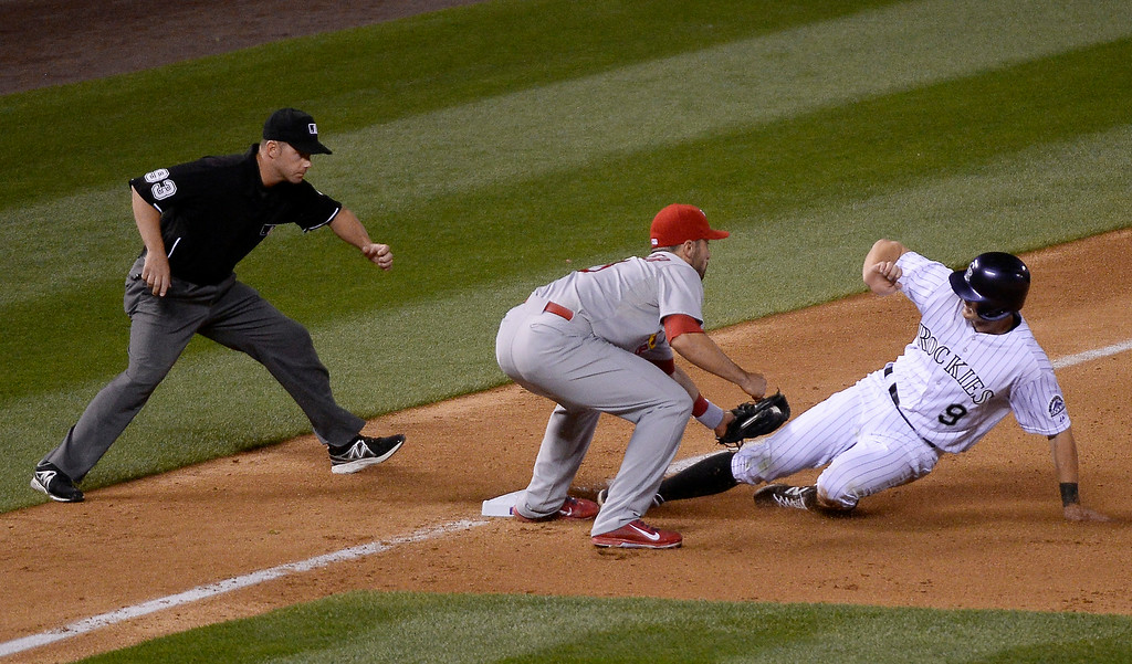 . DENVER, CO - JUNE 24: Colorado Rockies Colorado Rockies DJ LeMahieu (9) gets tagged out at third base by St. Louis Cardinals third baseman Matt Carpenter (13) on a throw from the pitcher St. Louis Cardinals relief pitcher Sam Freeman (71) in the seventh inning June 24, 2014 at Coors Field. (Photo by John Leyba/The Denver Post)