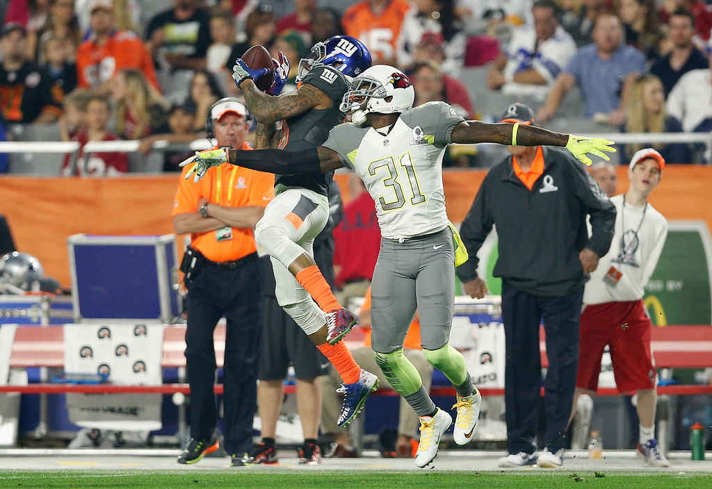 . GLENDALE, AZ - JANUARY 25: Team Irvin wide receiver Odell Beckham #13 of the New York Giants hauls in a pass over Team Carter cornerback Antonio Cromartie #31 of the Arizona Cardinals during the first half of the2015 Pro Bowl at University of Phoenix Stadium on January 25, 2015 in Glendale, Arizona.  (Photo by Christian Petersen/Getty Images)