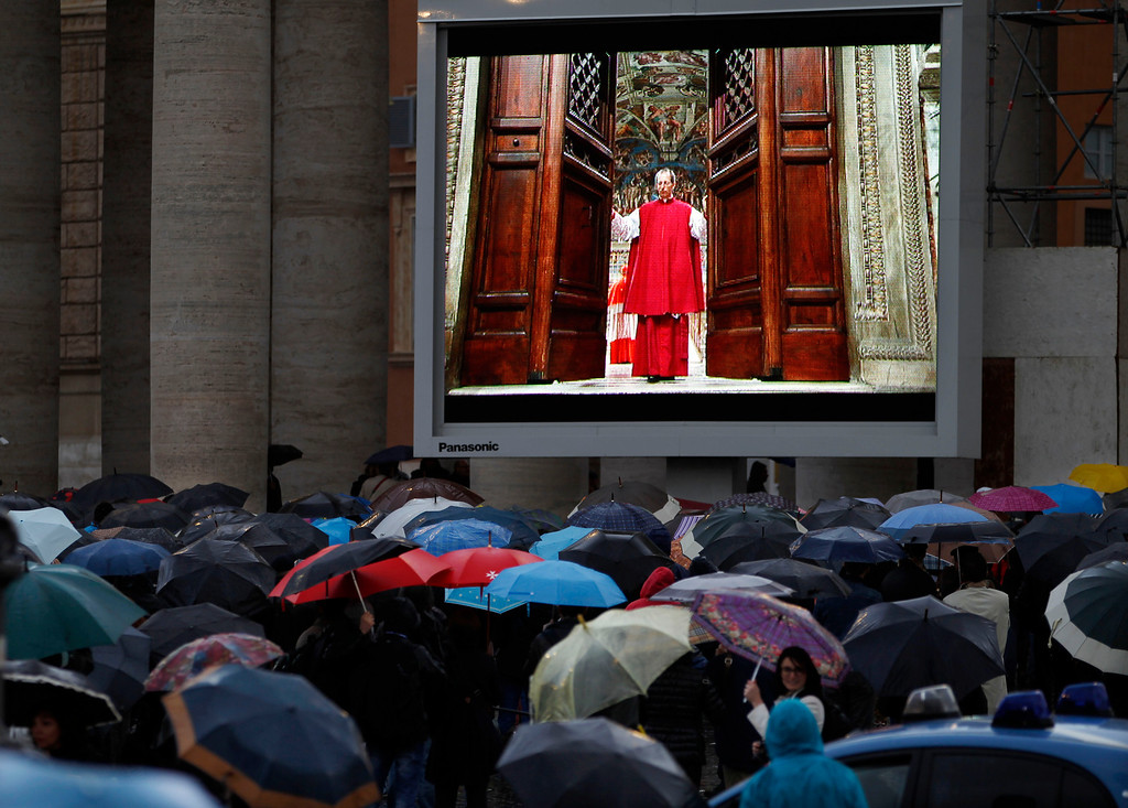 ". People watch on a video monitor in St. Peter\'s Square as Monsignor Guido Marini, master of liturgical ceremonies, closes the double doors to the Sistine Chapel after shouting ""Extra omnes,\"" Latin for \""all out,\"" telling everyone but those taking part in the conclave to leave the frescoed hall. He then locked it at the Vatican, Tuesday, March 12, 2013. (AP Photo/Michael Sohn)"