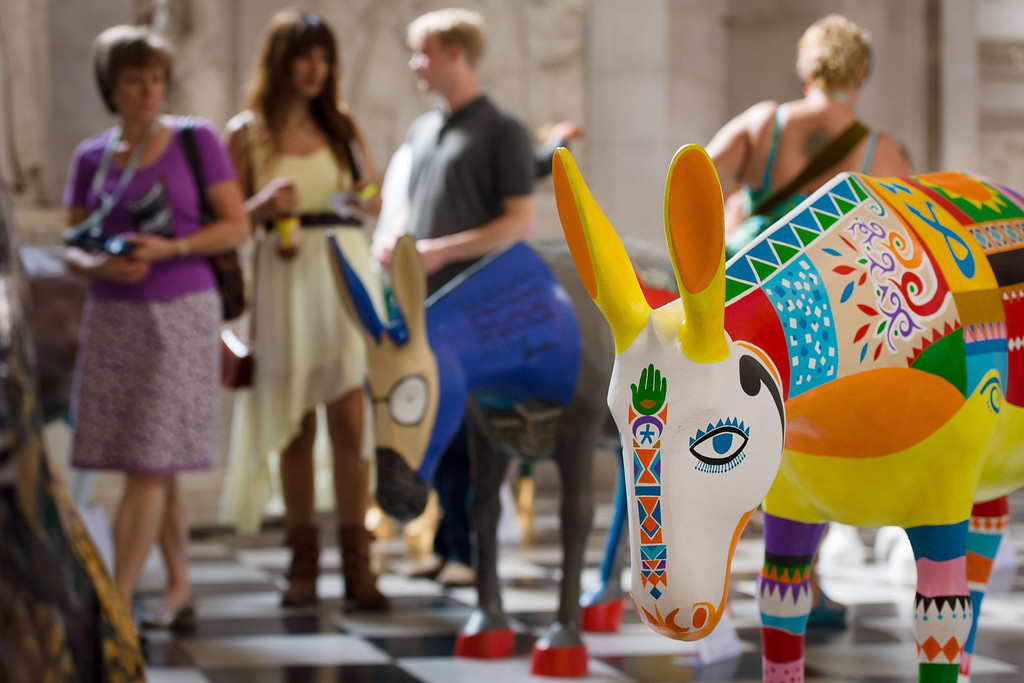 . Members of the public explore some of the 25 life-size painted donkeys, created by Egyptian and Western artists, as they go on display in St Paul\'s Cathedral in London on August 30, 2013.   AFP PHOTO / LEON NEAL/AFP/Getty Images